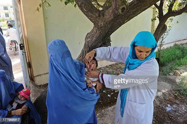 An Afghan health worker administers polio vaccine drops to a child during the second day of a vaccination campaign in Herat on August 26 2013 Polio...