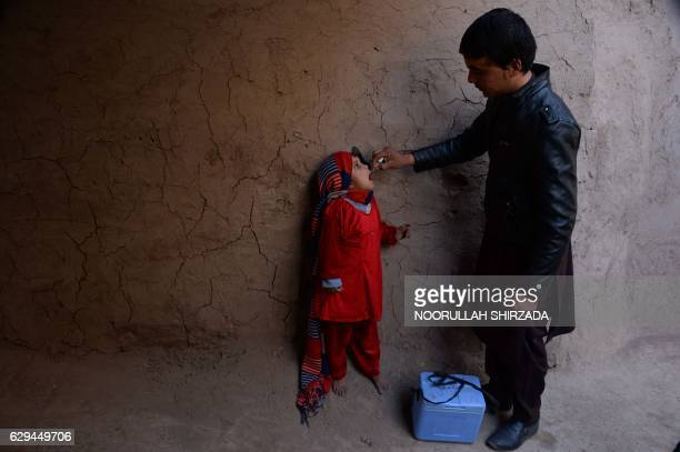 An Afghan health worker administers the polio vaccine to a child during a vaccination campaign on the outskirts of Jalalabad on December 13, 2016....