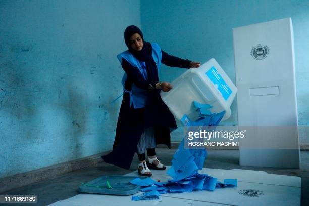 TOPSHOT An Afghan Independent Election Commission official empties a ballot box to count ballot papers after polling stations closed in Herat on...