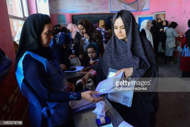 An Afghan Independent Election Commission official prepares ballot papers for voters at a polling centre for the country's legislative election in...
