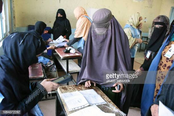 An Afghan Independent Election Commission official scans a voter with a biometric device at a polling centre for the country's legislative election...