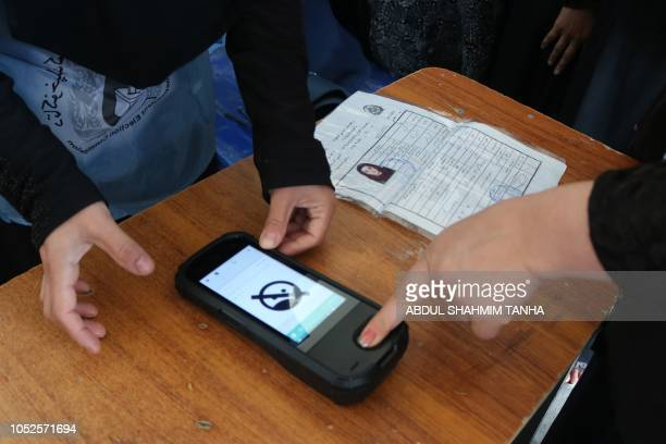 An Afghan Independent Election Commission official scans a voter's finger with a biometric device at a polling centre for the country's legislative...