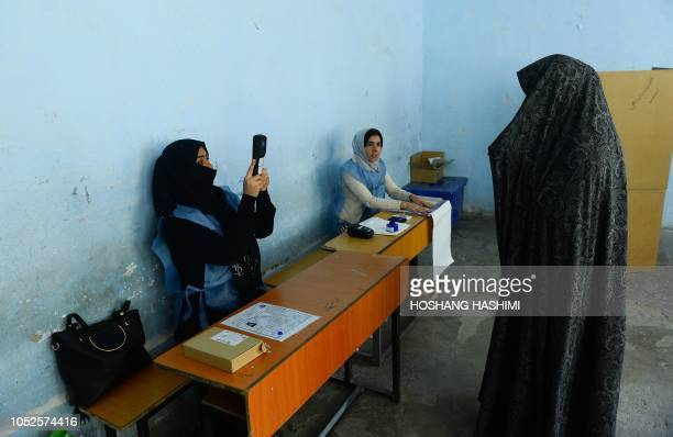 An Afghan Independent Election Commission official scans a voter's face with a biometric device at a polling centre for the country's legislative...