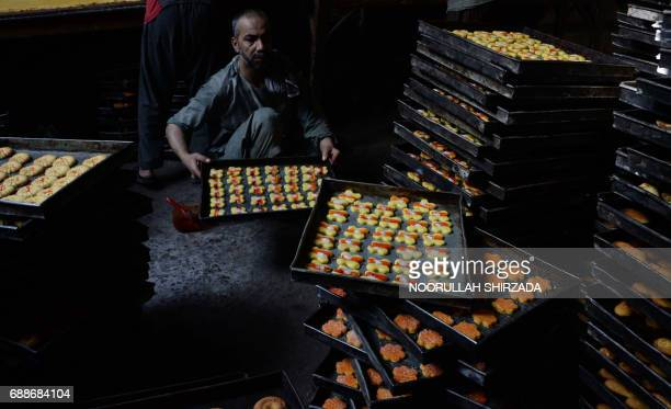 An Afghan labourer works at a traditional sweet factory ahead of the holy month of Ramadan in Jalalabad on May 26, 2017. Islam's holy month of...