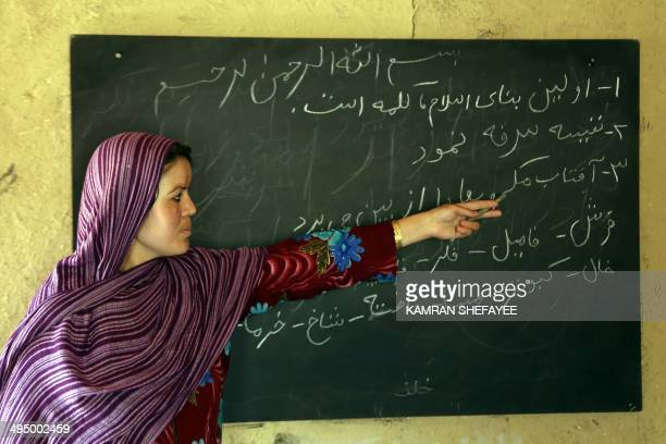 An Afghan literacy teacher pronounces words to students during a class in Bamiyan province on May 31 2014 Some 60 literacy training centres funded by...