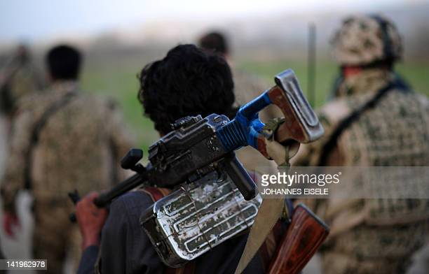 An Afghan Local Police carries his weapon as he walks with German Soldiers towards a bridge to meet a visiting military commander near Baghlan on...
