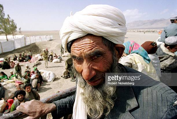An Afghan man and his family disembark from rented trucks as they arrive at the Maslakh refugee camp January 22 2001 in Herat Afghanistan Some of...