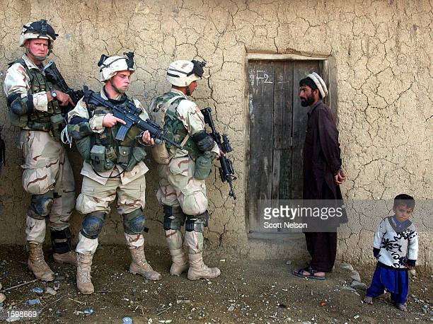 An Afghan man and his son watch as soldiers from the US Army 82nd Airborne Division prepare to sweep their home November 7 2002 in southeastern...