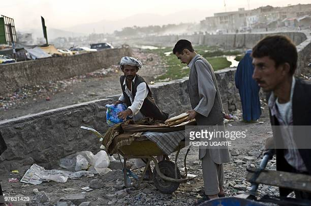 An Afghan man buys bread at the roadside in Kabul on August 18 2009 Afghans vote August 20 to choose a president for only the second time in history...