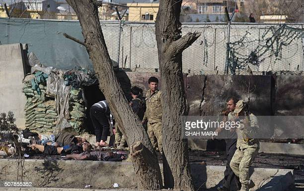An Afghan man carries a bomb victim as others are seen at the site of a suicide car bomb next to a police base in Kabul on February 1 2016 A suicide...