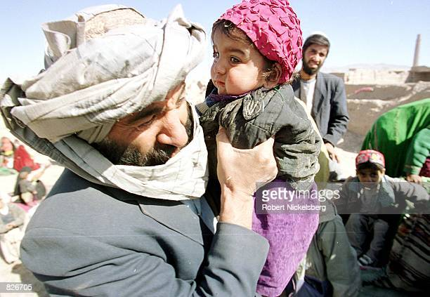 An Afghan man carries his child as they disembark from a truck upon their arrival at the Minarets refugee camp January 25 2001 in Herat Afghanistan...