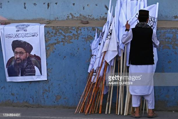 An Afghan man checks the Taliban flags kept for sale next to a poster of Taliban leader Abdul Ghani Baradar along a street in Kabul on August 27,...