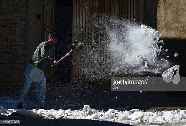 An Afghan man clears snow from the street in Kabul on February 16 2014 Some nine million Afghans or 36 percent of the population are living in...