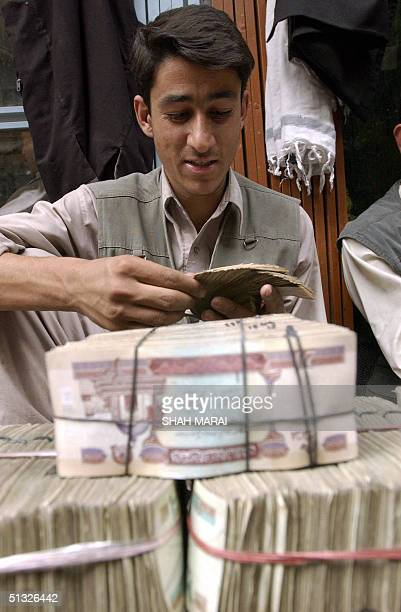 An Afghan man counts Afghanis he got from money changers at an outside market in Kabul 20 September 2004 Three weeks ahead of Afghanistan's first...