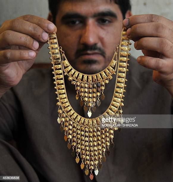 An Afghan man displays a gold necklace in a jewellery shop at a market in Jalalabad on August 14 2014 As the ongoing war in Afghanistan enters its...