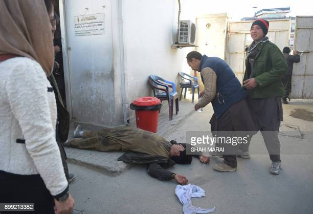 An Afghan man faints at a hospital following explosions at a Shiite cultural centre in Kabul on December 28 2017 At least 40 people were killed and...