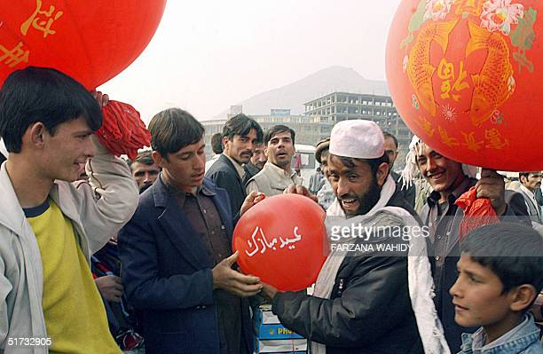 An Afghan man holds a balloon bearing the words 'Eid Mubarak' or Happy Eid at a market in Kabul 12 November 2004 as preparations begin for the...