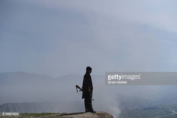 An Afghan man holds a gun as he keeps watch in DandeGhori district in Baghlan province on March 15 following weeks of heavy battles to recapture the...
