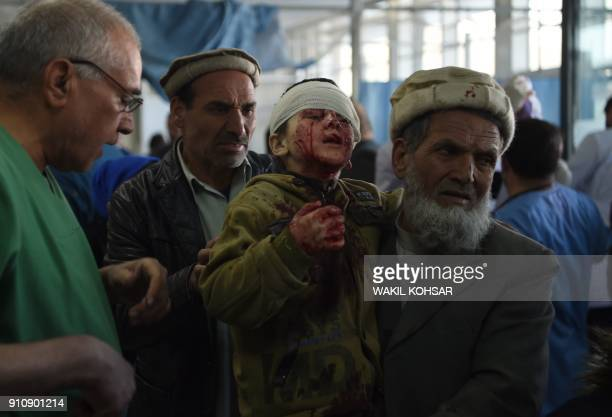 TOPSHOT An Afghan man holds a wounded child after a car bomb exploded near the old Interior Ministry building at Jamhuriat Hospital in Kabul on...