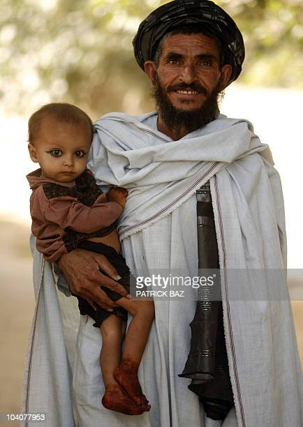 An Afghan man holds his son as he watches US army soldiers with the 101st Airborne Division Alpha Battery 1-320th and an Afghan National Army...