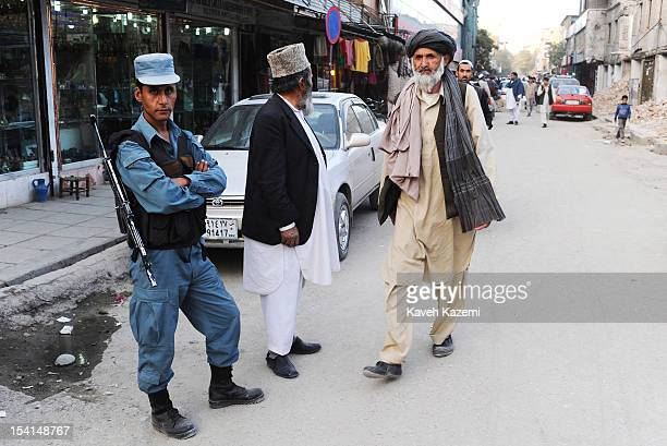 An Afghan man in typical clothing passes by an armed policeman standing by on duty in Chicken Street on October 17 2011 in Kabul Afghanistan Chicken...