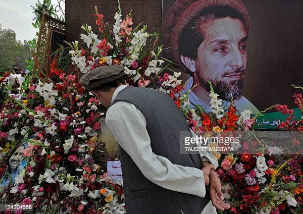An Afghan man looks at a portrait during a ceremony marking the tenth anniversary of the death of slain Afghan national hero Ahmad Shah Masood in...
