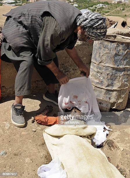 An Afghan man looks at the dead body of his relative a young boy killed in an explosion in Kabul on May 5 2008 Three Afghan children were killed when...