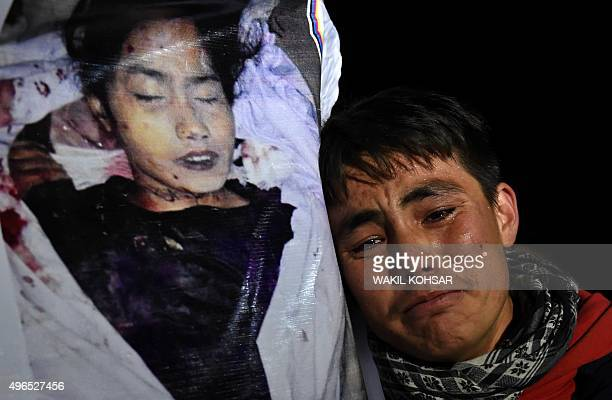 An Afghan man looks on next to a poster of one of a group of seven decapitated Shiite Hazaras including four men two women and one child during a...