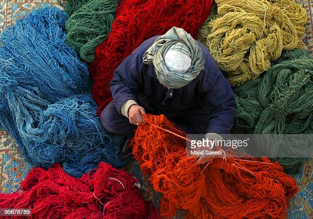An Afghan man organizes a pile of threads after being dyed at a carpet manufacturer on January 8 2010 in Kabul Afghanistan The highly prized and...