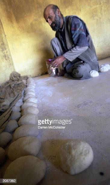 An Afghan man prepares dough at a bread making shop June 5 2003 in Kabul Afghanistan Bread is a staple food in the Afghan diet and is eaten at all...