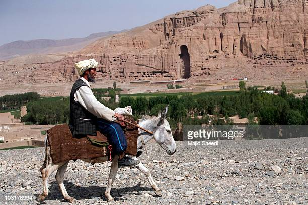 An Afghan man rides a donkey near the ruins of the ancient budha statues that once stood on July 30 2010 in the central Afghan province of Bamiyan...