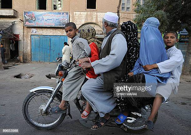 An Afghan man rides a motorcycle with five members of his family in the old city of Herat on August 7 2009 Afghans go to the polls on August 20 to...