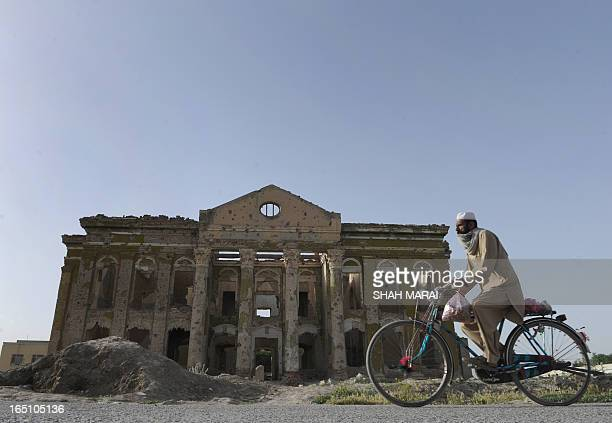 An Afghan man rides his bicycle past a building destroyed during the civil war in Kabul on May 19 2011 Taliban fighters attacked an Afghan road...