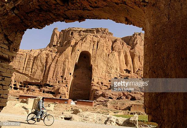 An Afghan man rids his bicycle in front of the empty seat of the Buddha destroyed by the Taliban in Bamiyan on July 7 2008 The cavemonasteries of...