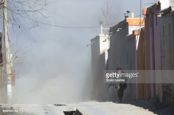 An Afghan man runs away as dust blows in the aftermath of the third blast at a Shiite cultural centre in Kabul on December 28 2017 At least 40 people...