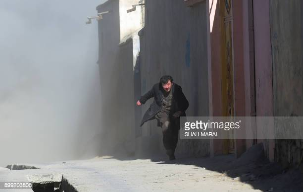 TOPSHOT An Afghan man runs away as dust blows in the aftermath of the third blast at a Shiite cultural centre in Kabul on December 28 2017 At least...