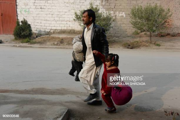 TOPSHOT An Afghan man runs with two children near an office of the British charity Save the Children during an ongoing attack in Jalalabad on January...