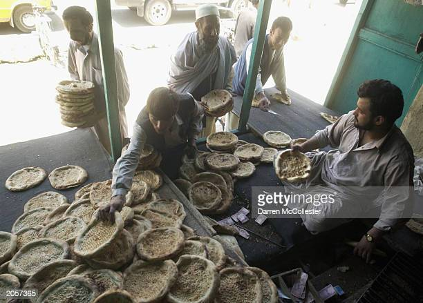 An Afghan man sells bread outside a bread making shop June 5 2003 in Kabul Afghanistan Bread is a staple food in the Afghan diet and is eaten at all...