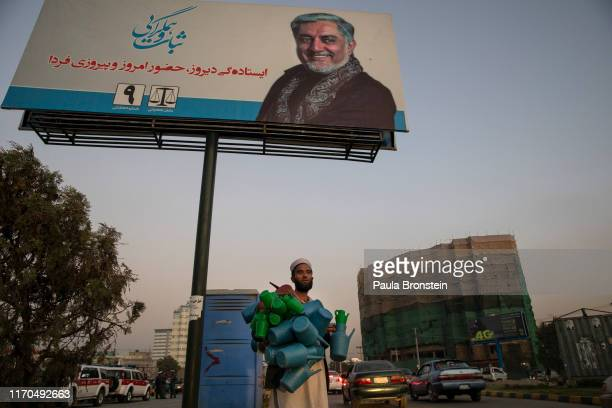 An Afghan man sells water jugs next to a giant election billboard of Abdullah Abdullah Chief Executive of Afghanistan who is running for President on...