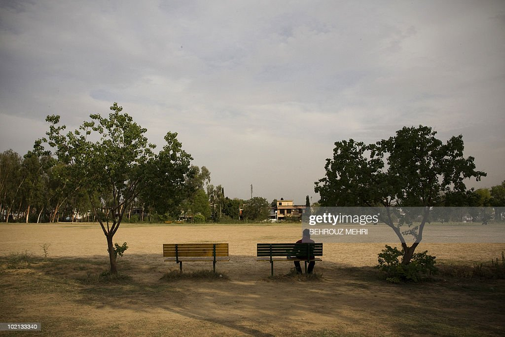 An Afghan man sits on a park bench in Islamabad on June 15, 2010.