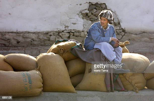 An Afghan man sits on top of free wheat handed out by the World Food Program December 27 2001 in Kabul Afghanistan The World Food Program handed out...