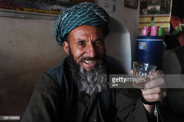 An Afghan man smiles as he drinks a cup of tea at a tea house in the eastern city of Herat on September 30 2012 Tea is a major drink in Afghanistan...