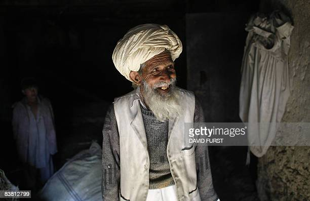 An Afghan man stands in his doorway as US Army soldier from 2-506 Infantry 101st Airborne Division and Afghan National Policemen arrive to search his...