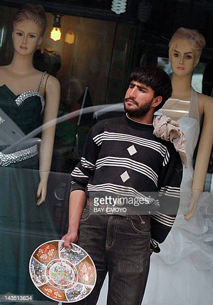 An Afghan man stands on a sidewalk in front of mannequins in Kabul on April 28 2012 Poverty and an ongoing insurgency by the ousted Taliban still...