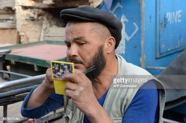 An Afghan man trims his beard in the old part of Kabul on September 16 2017 / AFP PHOTO / NOORULLAH SHIRZADA
