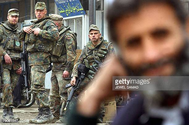 An Afghan man waits for transport as German soldiers of the International Security Assistance Force rest during a patrol in Kabul, 23 February 2003....