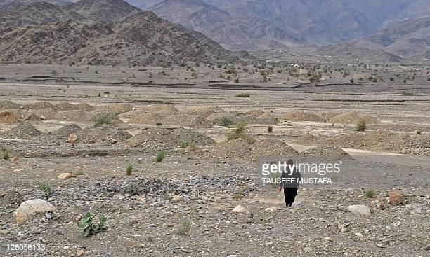 An Afghan man walks across rocky terrain in the Turkham Nangarhar region of Afghanistan bordering Pakistan on October 5 2011 Turkham is a border...