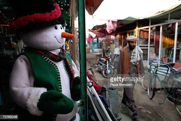 An Afghan man walks by a snowman at the Bush Bazaar October 29 2006 in Kabul Afghanistan The small black market named after US President George W...