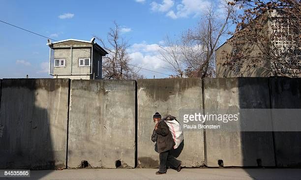 An Afghan man walks by blast walls near the Indian embassy now a high security zone January 29 2009 in Kabul Afghanistan Afghan officials postponed...