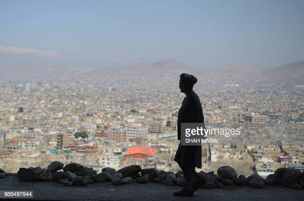 TOPSHOT An Afghan man walks during the first day of the Nowruz or Persian New Year in a hilltop overlooking of Kabul on March 21 2018 / AFP PHOTO /...